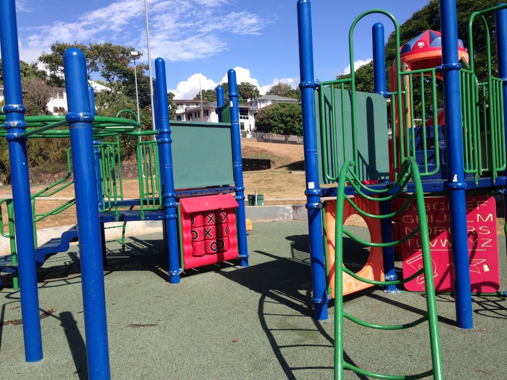 Local Neighborhood Park Missing the foot bridge that connects the two play structures. Green plywood blocks entry points where bridge once sat, to prevent falling.
